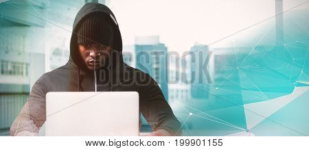Serious male hacker with laptop  against blue abstract design