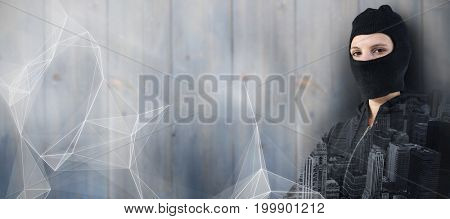 Portrait of female hacker standing with arms crossed against abstract black background