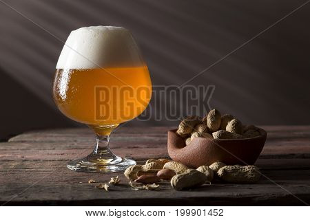 Glass of cold light unfiltered beer and a bowl of peanuts on a rustic wooden pub table. Focus on the froth