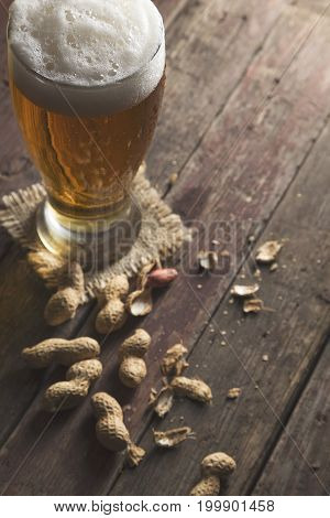 Glass of pale beer with froth and some peanuts on a rustic wooden pub table. Focus on the froth