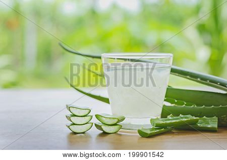 fresh aloe vera leaves and aloe vera juice in glass on wooden background