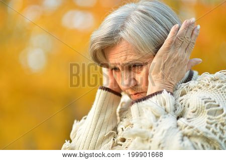 senior beautiful  sad woman with headache outdoors