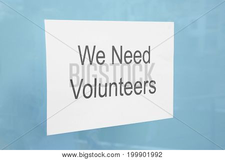 Sheet of paper with text WE NEED VOLUNTEERS on window glass