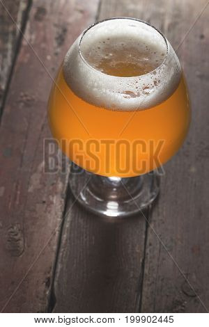 Glass of cold light unfiltered beer on a rustic wooden table. Selective focus on the froth