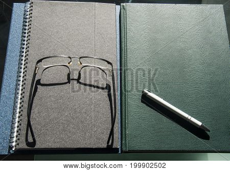 books and notebooks piled up with pen and glasses