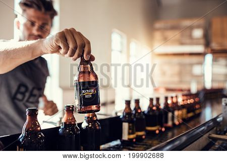 Young man examining the quality of beer. Beer bottles moving on conveyor belt in brewery factory with brewer testing the bottles.