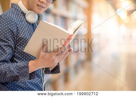 Young Asian man university student reading book in library education research and self learning in university life concepts