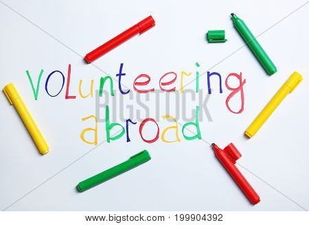 Text VOLUNTEERING ABROAD and felt-tip pens on white background