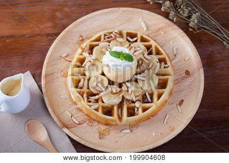 Waffle With Banana And Ice-cream Vanilla On Top Has Whip Cream And Peppermint Sprinkle With Almonds