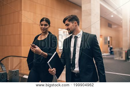 Two young people walking together in airport terminal. Business travelers at airport.