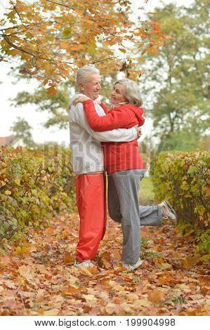 Happy senior couple dancing  in autumn park
