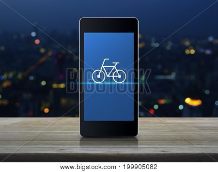 Bicycle flat icon on modern smart phone screen on wooden table over blur colorful night light of city tower Bike shop online concept