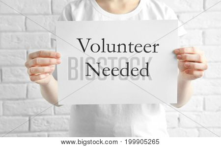 Woman holding sheet of paper with text VOLUNTEER NEEDED on light background