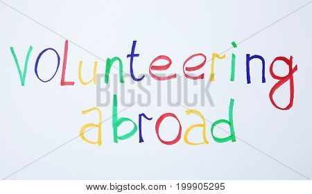 Text VOLUNTEERING ABROAD on white background