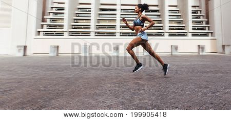 Woman athlete running outdoors in the morning. Woman in running outfit sprinting in the street.