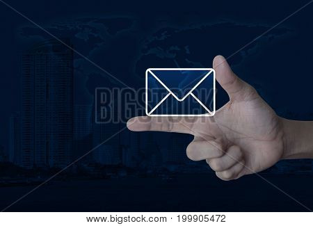 Mail icon on finger over world map and modern city tower Contact us concept Elements of this image furnished by NASA