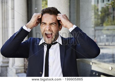 Businessman in suit shouting in rage and frustration
