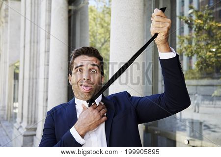 Businessman frustrated strangled by his tie portrait