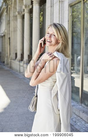 Fashionable woman receiving good news call in city smiling