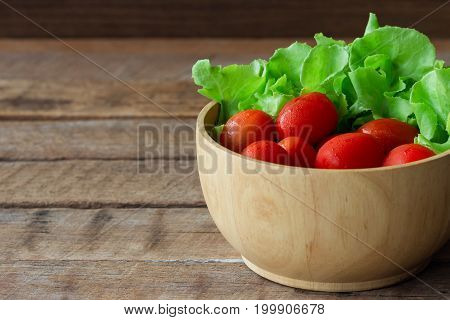Fresh Tomato And Lettuce In Wood Bowl Put On Wood Table. Side View Close Up Of Tomato And Green Oak