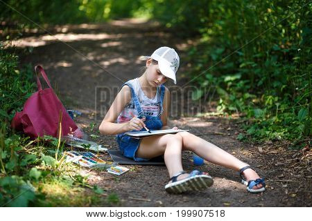 Girl Artist Paints In The Park In The Open Air.