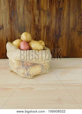 Potatoes in a sack on a wooden background. Harvest picking concept