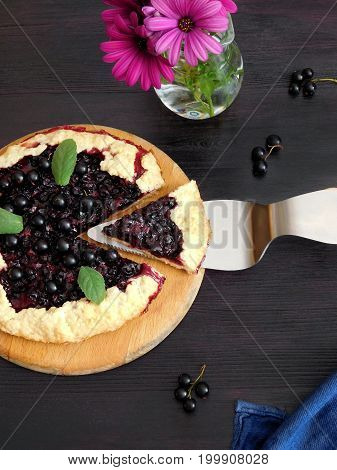 Galette with black currant and a piece of it on a dark background