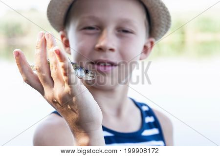 Young boy holding in his hand fish small zander