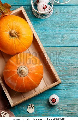 Halloween pumpkins, wooden skulls, maple leaves, eyeballs on blue wooden table