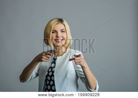 Beautiful smiling blonde showing fingers in camera in studio
