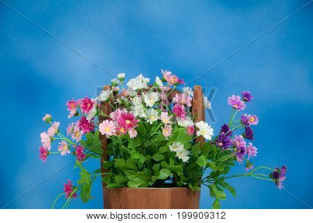 Bright And Beautiful Colors Of Plastic Flowers In Wood Bucket On Blue Background In Studio