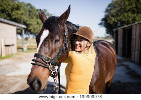 Portrait of smiling female jockey stroking horse at stable