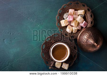 Traditional turkish coffee  and turkish delight on dark green wooden background. flat lay