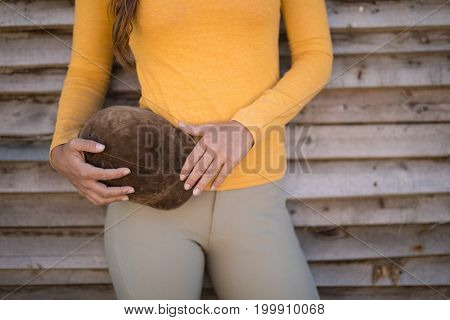 Midsection of female jockey holding helmet while standing by wodoen wall