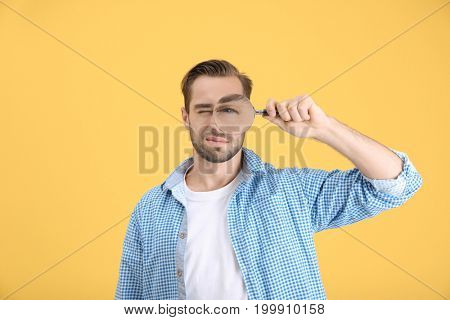 Handsome young man with magnifier on color background