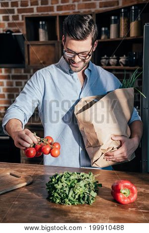 Handsome Smiling Young Man Unpacking Vegetables At Kitchen