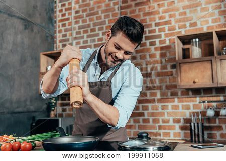 Handsome Young Man Adding Pepper Into Frying Pan