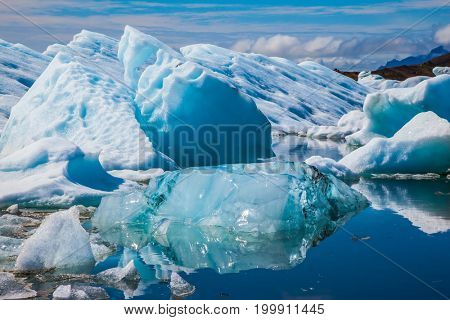 Gorgeous morning light in the Ice Lagoon. Icebergs and ice floes are reflected in the smooth water surface. The concept of extreme northern tourism