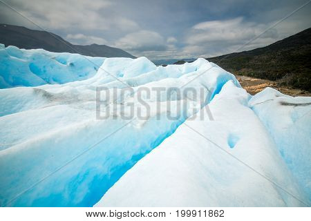 The surface of the glacier against the background of mountains and cloudy weather. The blue glacier rises and shines in the daylight. The slopes of the blue glacier in the sunlight. Beautiful blue glacier against the sky. Uneven surface of the glacier in
