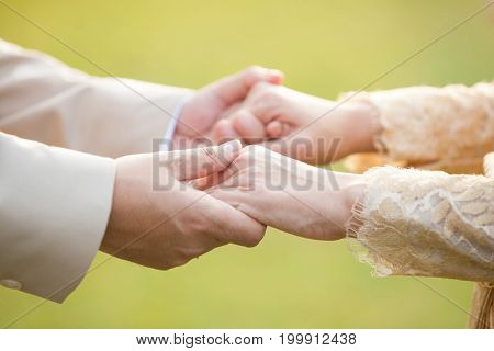 Close-up Holding Hands Of Lovers On Wedding Day In Thailand
