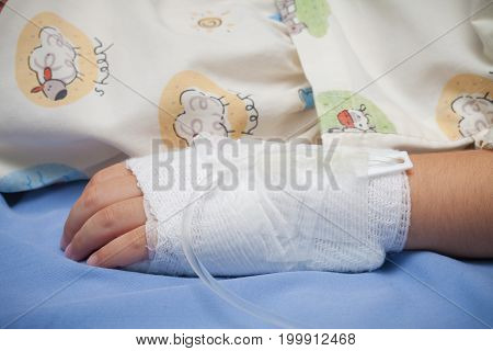 Closeup Hand Of Kid Sick With The Salt Water Tube On The Bed In Hospital