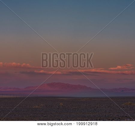 panoramic view of beautiful green plain at root of mountains at dusk
