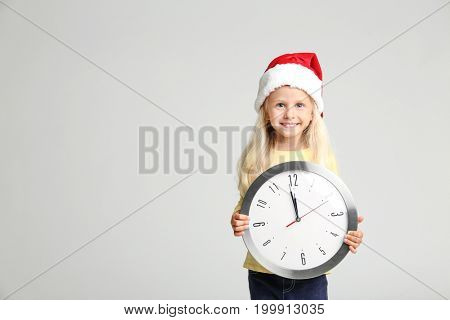 Cute little girl in Santa hat with clock on light background. Christmas countdown concept
