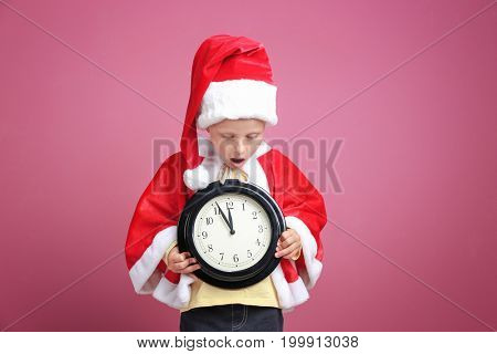 Cute little girl in Santa Claus suit with clock on color background. Christmas countdown concept