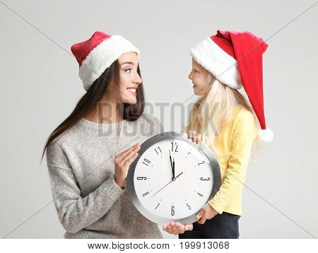 Young woman and cute girl in Santa hats with clock on light background. Christmas countdown concept