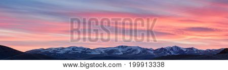 panoramic view of snow-capped mountain ranges at dusk