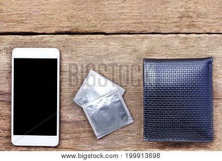 condoms wallet and mobile phone on wooden table.