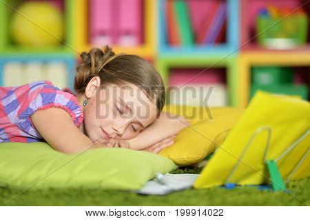 Portrait of a tired schoolgirl sleeping on exercise book
