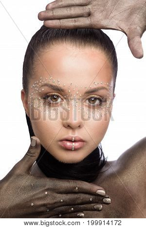 Brunette beautiful woman with crystals on face. Fashion creative black make-up on neck and hands with Swarovski. finger frame