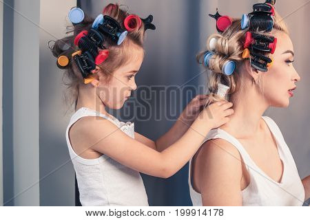 Beautiful young mother and her daughter with hair curlers are spending time together at home. The daughter removes curlers from her mom's hair